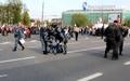 Артем Савелов. Омоновец роняет рацию. Рядом задерживают человека полицейские в серой форме. Кадр видео