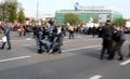Артем Савелов. Омоновец поднимает рацию. Рядом проводят задержание полицейские в серой форме. Кадр видео