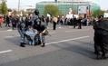 Артем Савелов. Омоновцы, продолжая заламывать ему руки, пытаются поднять его. Рядом проводят задержание сотрудники в серой форме. Кадр видео